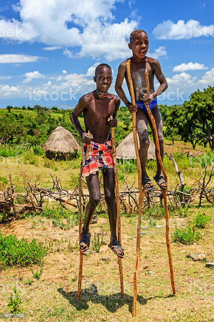 Two young boys walking on stilts, Ethiopia, Africa stock photo