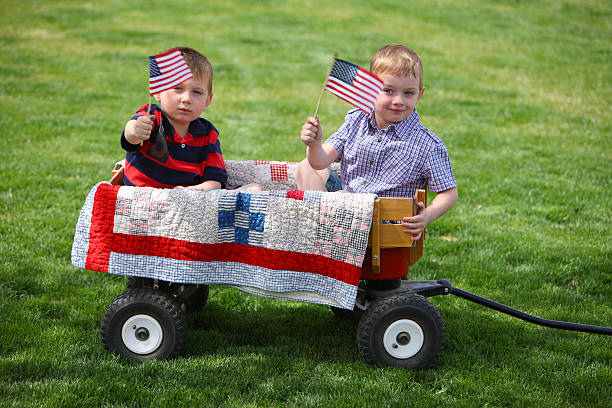 Two young boys waving American flags stock photo