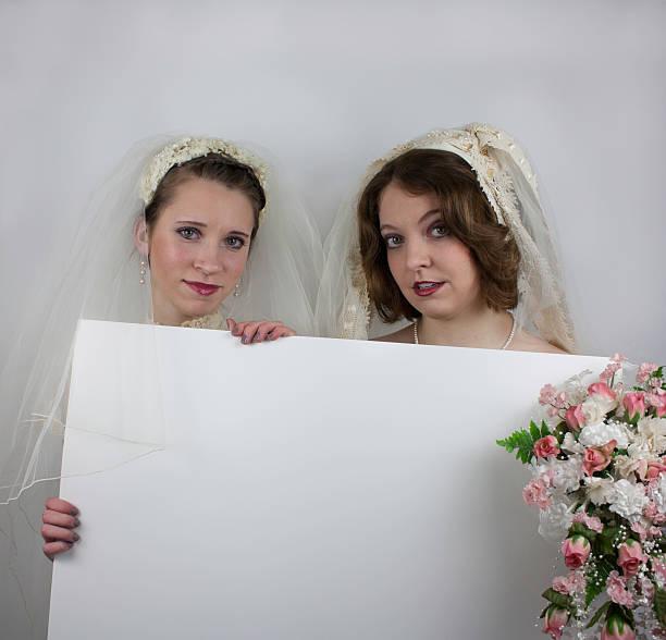 zwei junge braut holding blank sign - hochzeitskleid marken stock-fotos und bilder