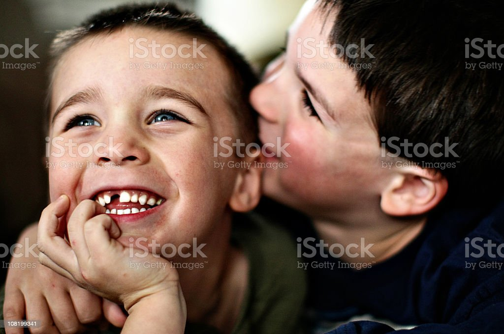 Two young brothers smiling and cuddling stock photo