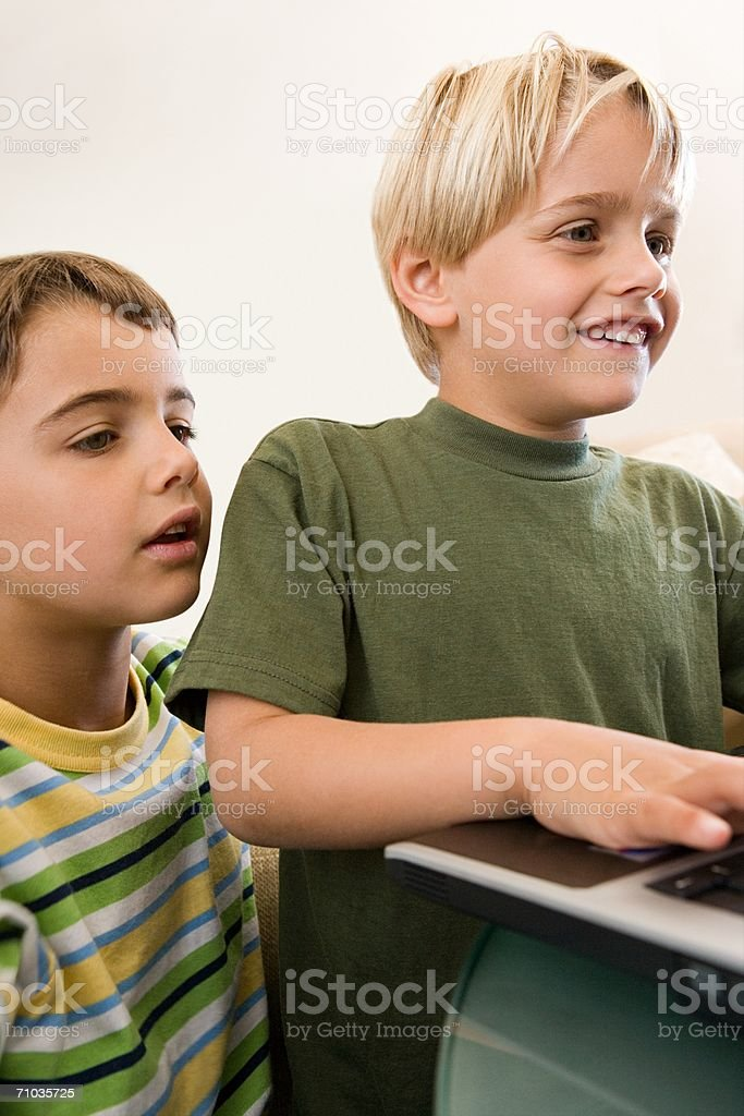 Two young brothers using a laptop computer royalty-free stock photo