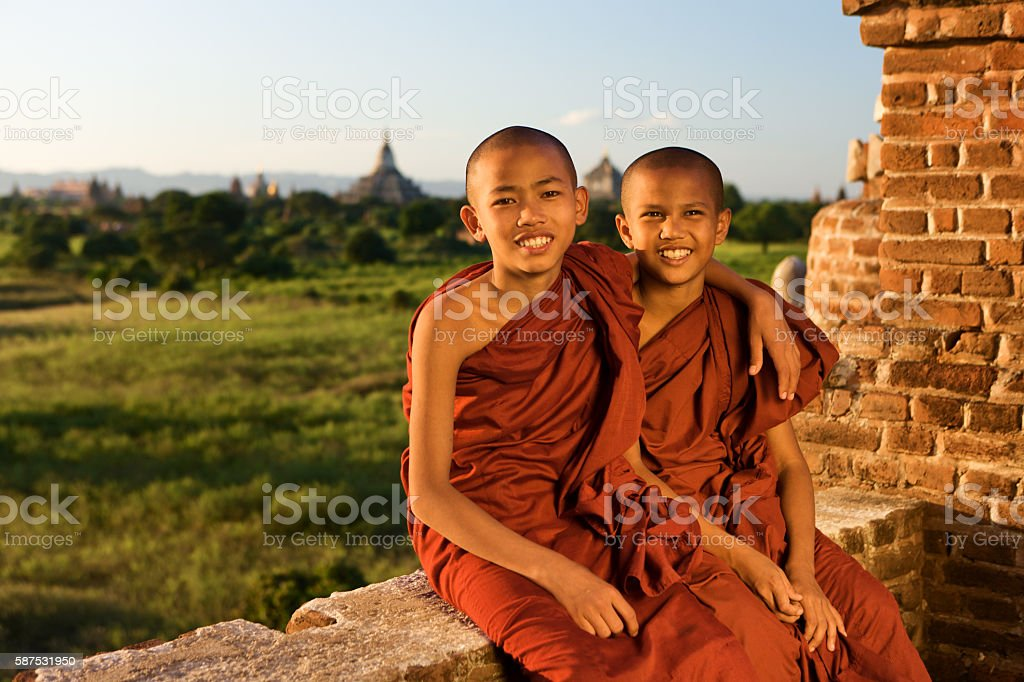 Two young Buddhist monks sitting on a stupa in Bagan stock photo