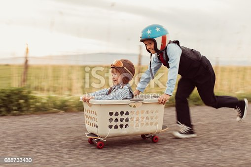 Two young boys are dressed in business attire race with excited expressions on their faces in a basket on a skateboard. The males are excited for new business opportunities and are ready for success. Image taken in Utah, USA.