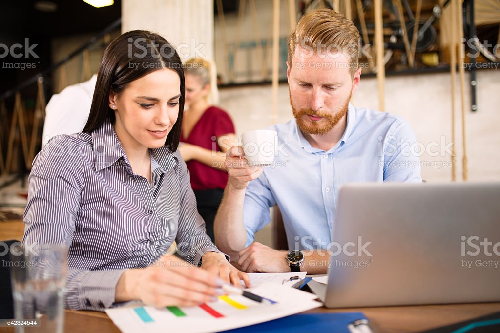 Two young pensive business people are analyzing graphs during coffee...