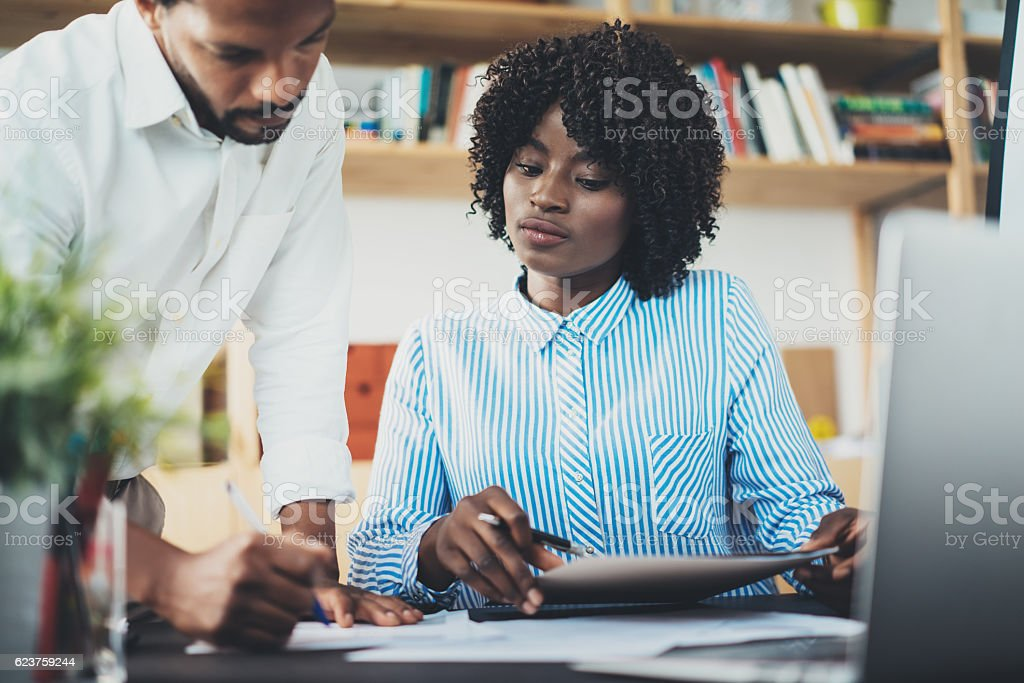 Two young business people working together in a modern office stock photo