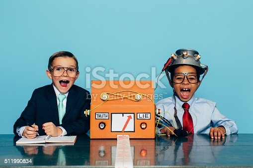Two young boys in business attire and glasses sitting at an office desk administer the lie detector test. The boys are surprised at the truth and untruth. You can never get too much practice for a job interview.