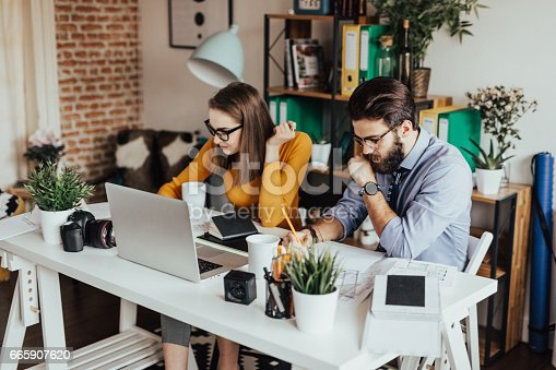 923634538 istock photo Two young businessman working together on a project 665907620