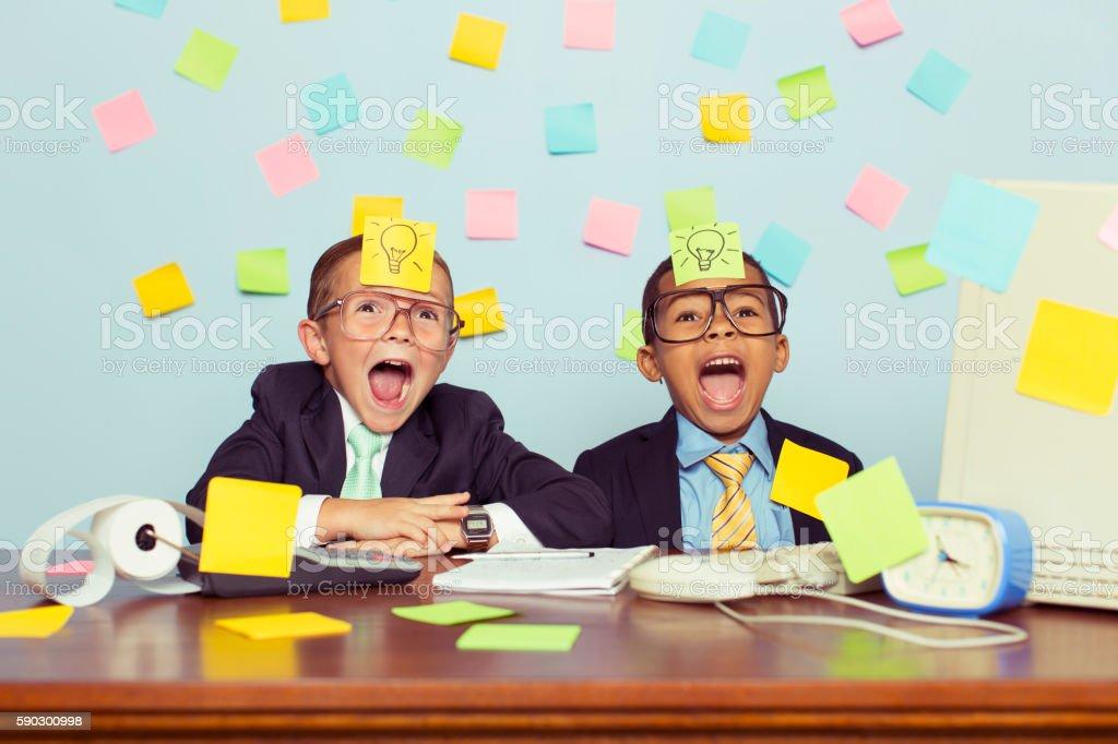Two Young Businessmen at Desk Covered with Sticky Notes royaltyfri bildbanksbilder