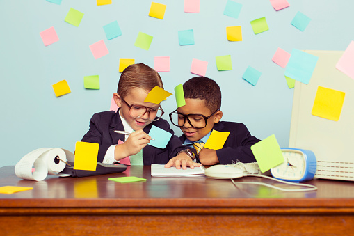 Two young businessmen sit at their office computer desk with pen in hand and express new business ideas on paper. They are forgetting many tasks for their business operations, and the wall behind them is covered in blank sticky notes. They are wearing a suit and tie and glasses, and blank sticky notes on them.