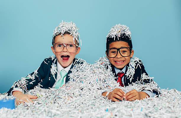 two young businessmen boys covered in shredded paper - shredded paper stock photos and pictures