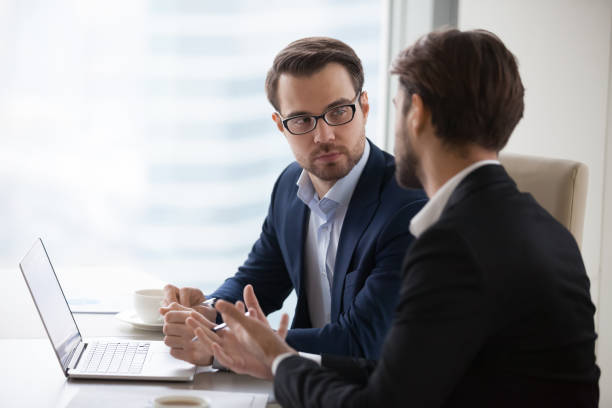 two young businessmen discuss or plan project in office - stock broker stock photos and pictures
