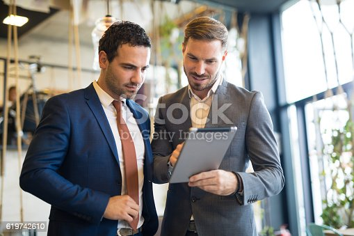 istock Two young businessmen discussing business strategy using digital tablet 619742610