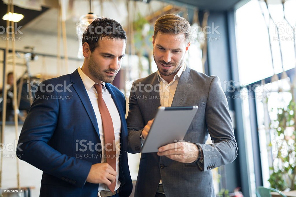 Two young businessmen discussing business strategy using digital tablet stock photo