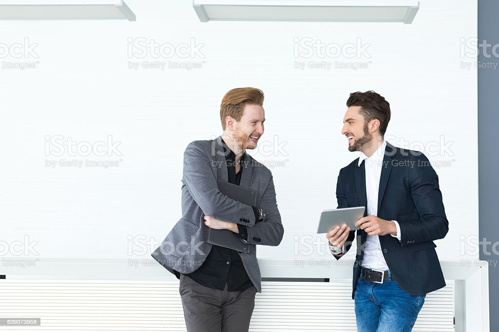 Two young businessmen discussing documents and reports. stock photo
