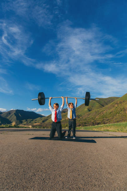 two young businessmen lifting weights together - resilience concept stock photos and pictures