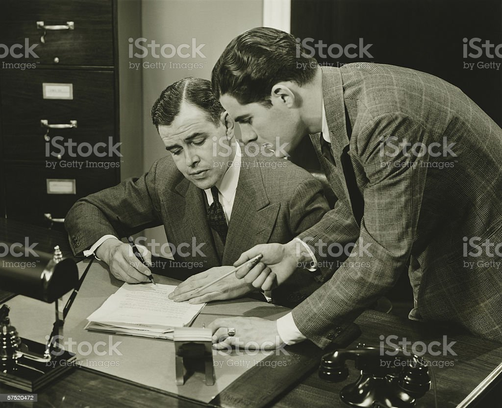 Two young businessmen talking at small desk, (B&W) stock photo