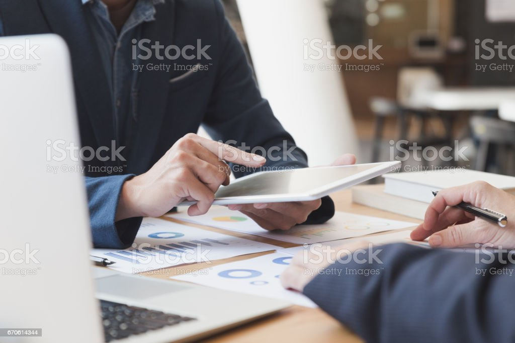 Two Young Businessmen Using Touchpad And Analysis Business Chart Document  At Meeting Stock Photo & More Pictures of Adult