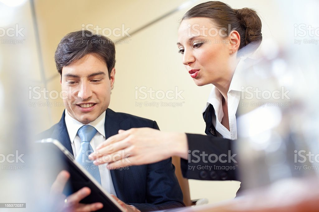 Two young businesspeople surfing the net on a digital tablet royalty-free stock photo