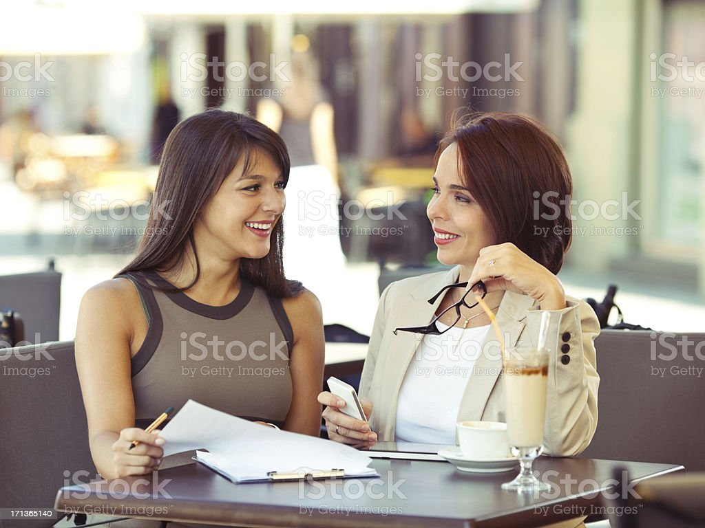 Two young businesswoman discussing in a cafe royalty-free stock photo