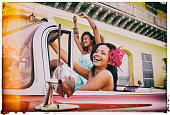 Vintage image of two young caribbean woman in an antique car in Trinidad, Cuba.