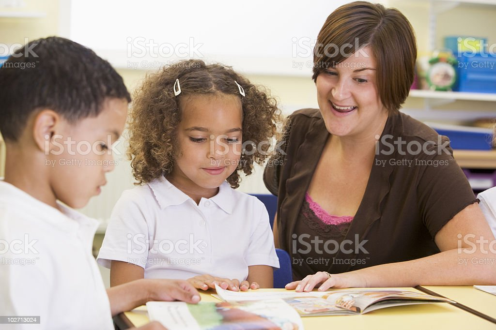 Two young children and their teacher reading stock photo
