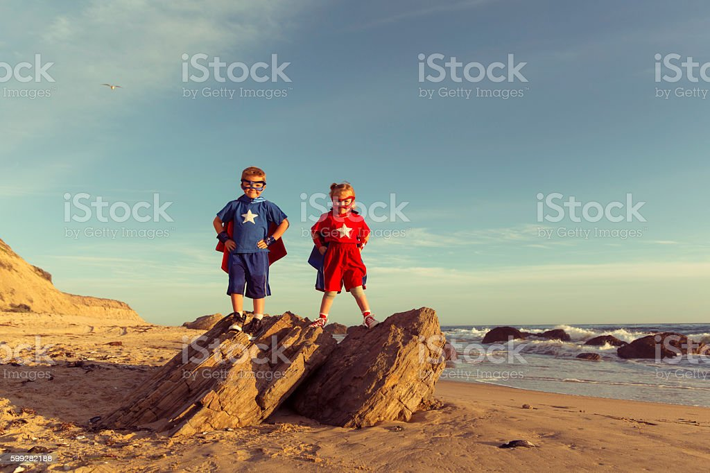 Two Young Children Dressed as Superheroes Stand on Rock stock photo