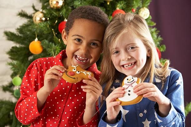 zwei junge kinder essen christmas leckereien - weihnachten 7 jährige stock-fotos und bilder