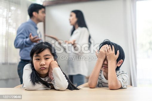 Two young children feeling sad and boring due to parents fighting at home. Older sister feels disappointed and sibling brother crying on father and mother aggressive trouble. Unhappy problem in family