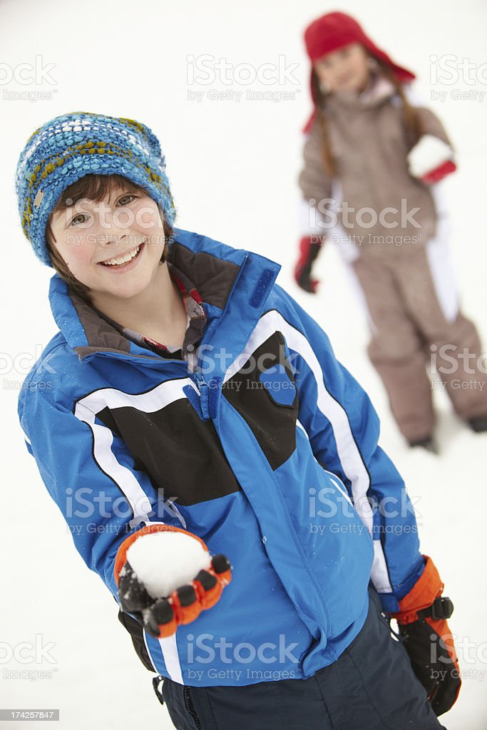 Two Young Children Having Snowball Fight Wearing Woolly Hats stock photo