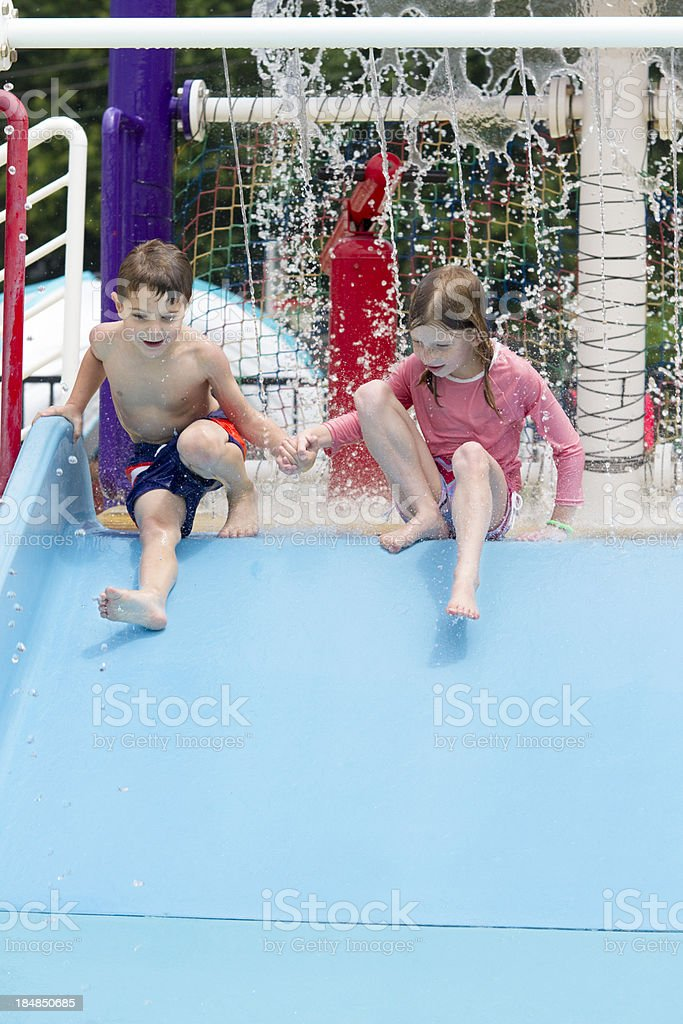 Two Young Children Playing At Swimming Pool Slide, Water Park royalty-free stock photo
