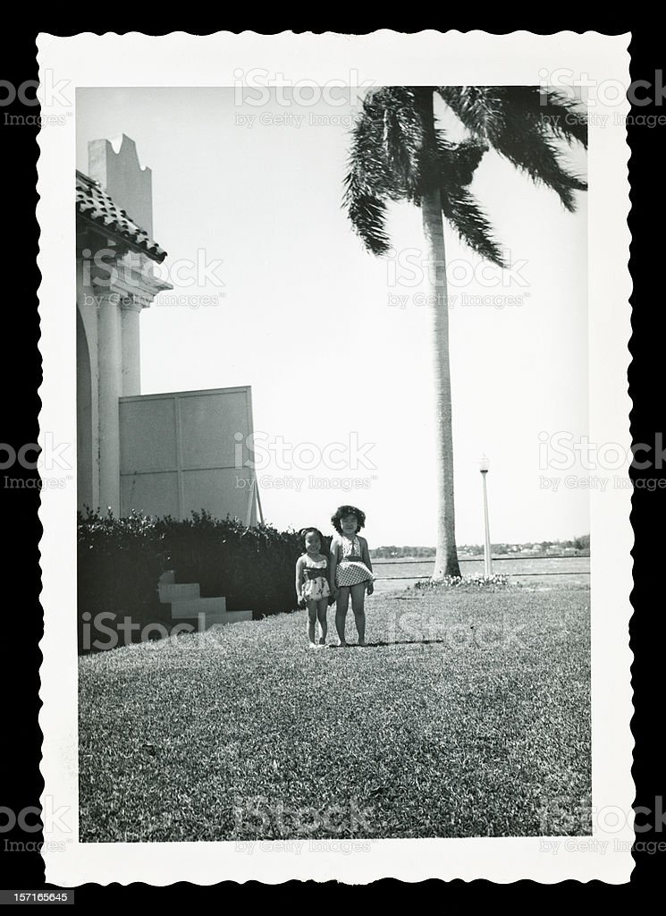 Two Young Children Playing Outside by a Palm Tree royalty-free stock photo