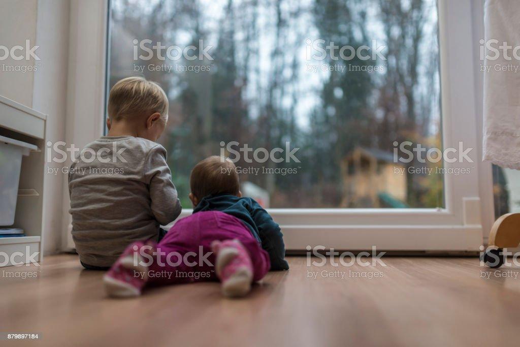 Zwei kleine Kinder sitzen an einer Glastür – Foto