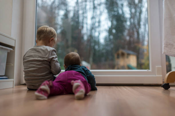 Two young children sitting at a glass door Two young children sitting and lying on the wooden floor in front of a glass door. real life stock pictures, royalty-free photos & images