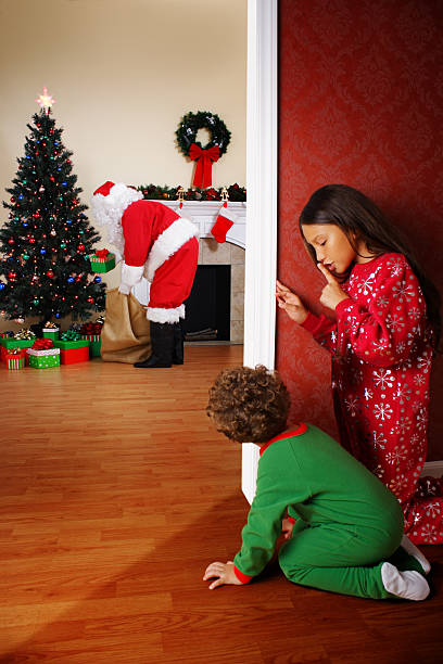 Two Young Children Spying on Santa Claus stock photo