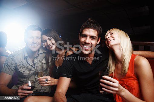 1072207668istockphoto Two young couple with drinks having fun at night club 183304690