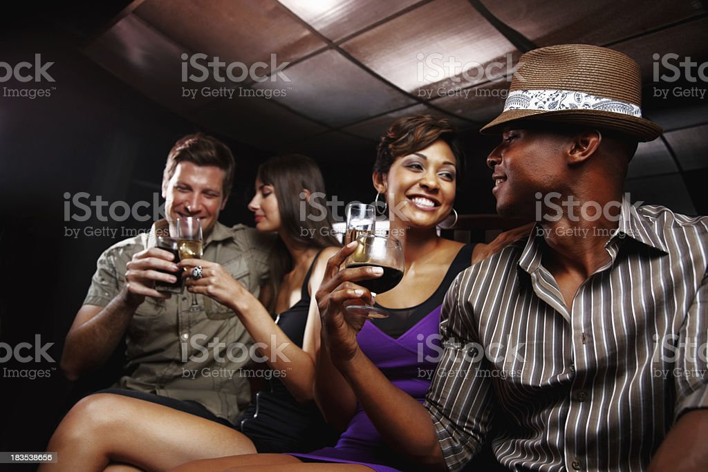 Two young couples with drinks, having fun at a nightclub royalty-free stock photo