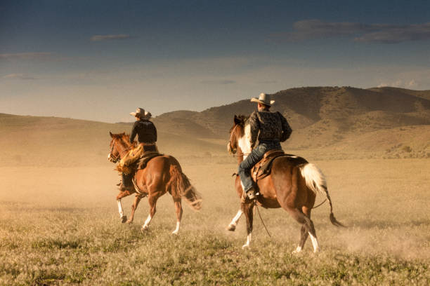 Two young cowboys riding together during the running of the horses in beautiful Utah. stock photo