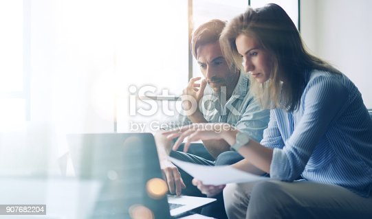 istock Two young coworkers working on laptop computer at sunny office.Woman holding paper documents and pointing on notebook screen. Horizontal.Blurred background. 907682204