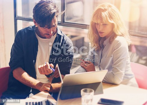 istock Two young coworkers working on laptop computer at sunny office.Woman holding paper documents and pointing on notebook screen. Horizontal.Blurred background.Cropped 912688178