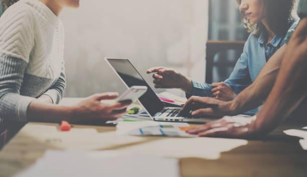 Zwei junge Kollegen arbeiten auf Laptop-Computer im Büro. Frau hält Smartphone und Notebook-Bildschirm zeigen. Horizontale. – Foto
