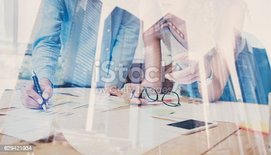 629421870 istock photo Two young coworkers working on wooden table in modern coworking 629421934
