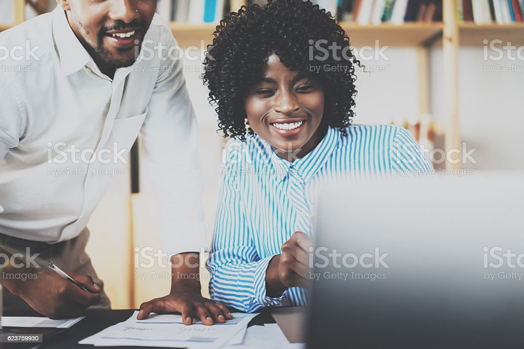 Two young coworkers working together in a modern office.African stock photo