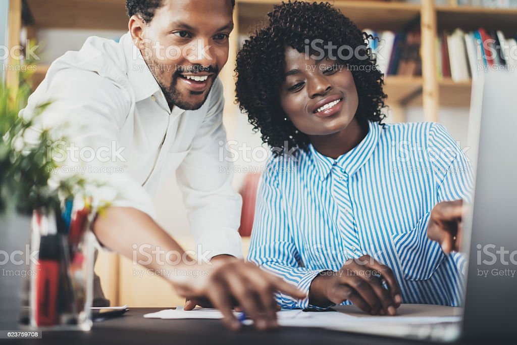 Two young coworkers working together in a modern office.Black stock photo