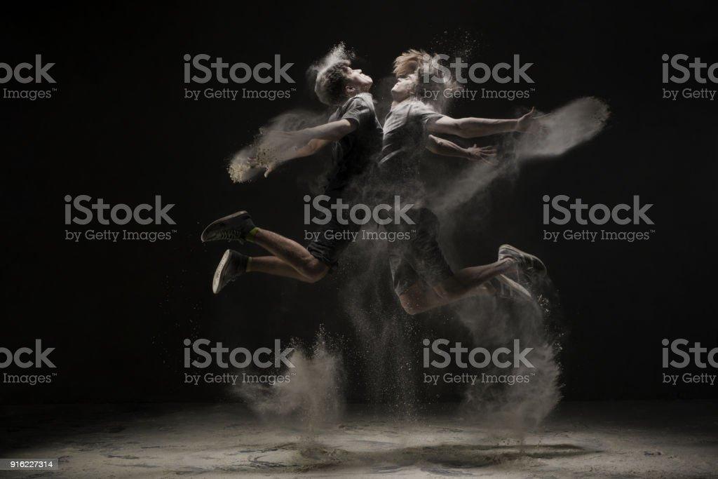 Zwei junge Tänzerinnen, die springen in Staubwolke anzeigen – Foto