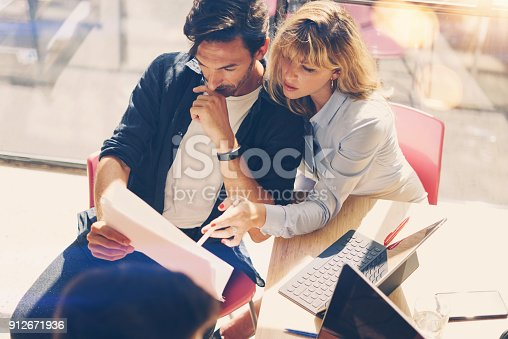 istock Two young entrepreneurs are looking for a business solution during work process at sunny office.Business people meeting concept.Blurred background.Horizontal. 912671936