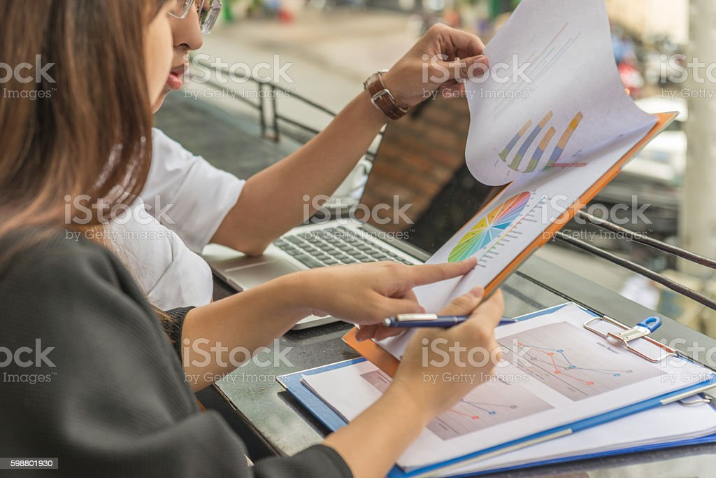 Two young entrepreneurs focus on the chart of income stock photo