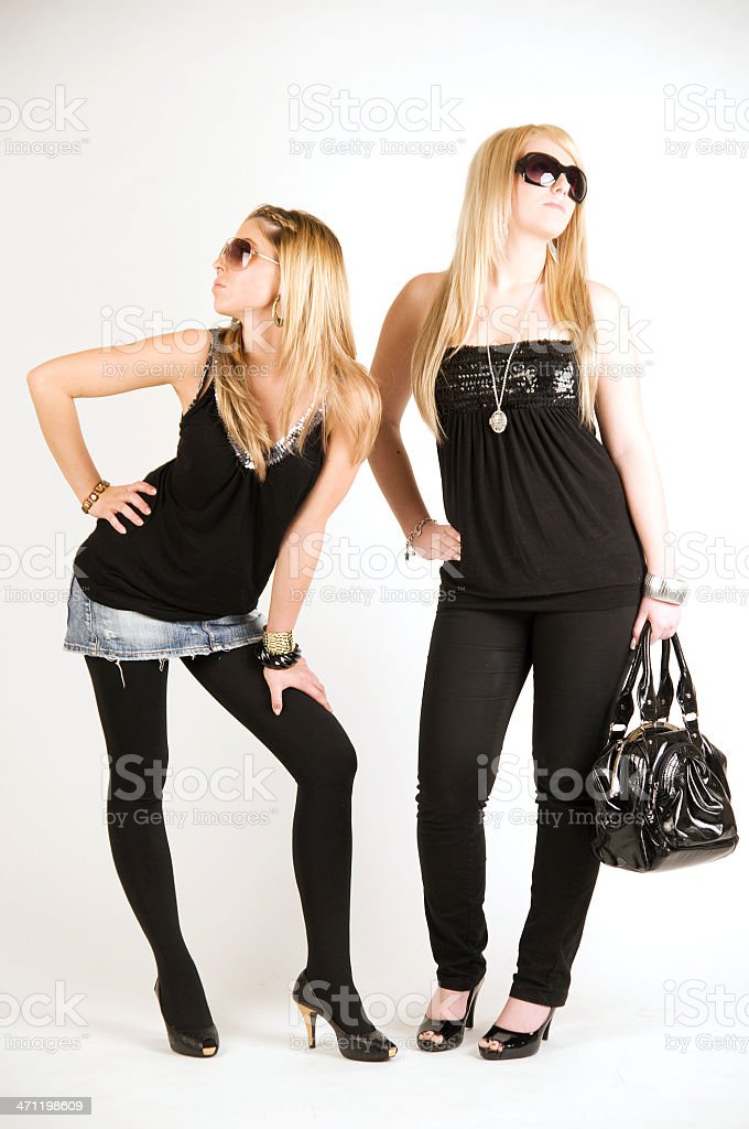 Two young fashion girls in studio. royalty-free stock photo