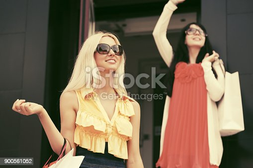 istock Two young fashion women with shopping bags at the mall 900561052