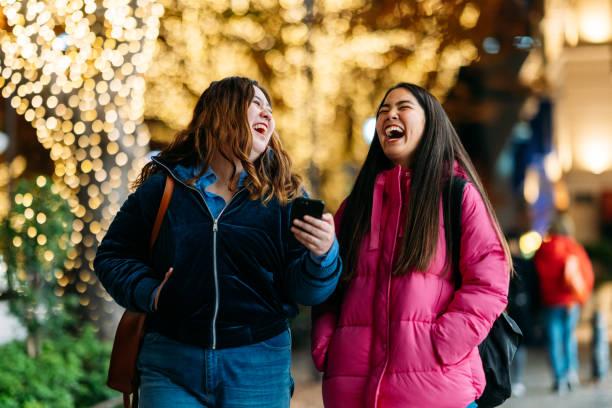 通りで夜の時間を楽しむ2人の若い女友達 - real bodies ストックフォトと画像