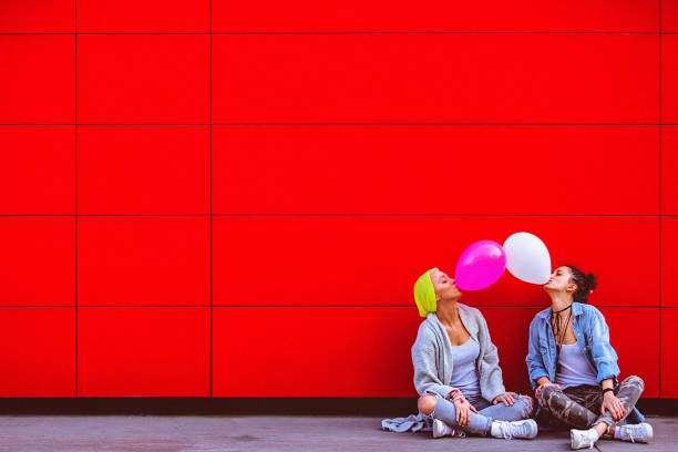 Two young female friends having fun, blowing up balloons in front of the red wall stock photo